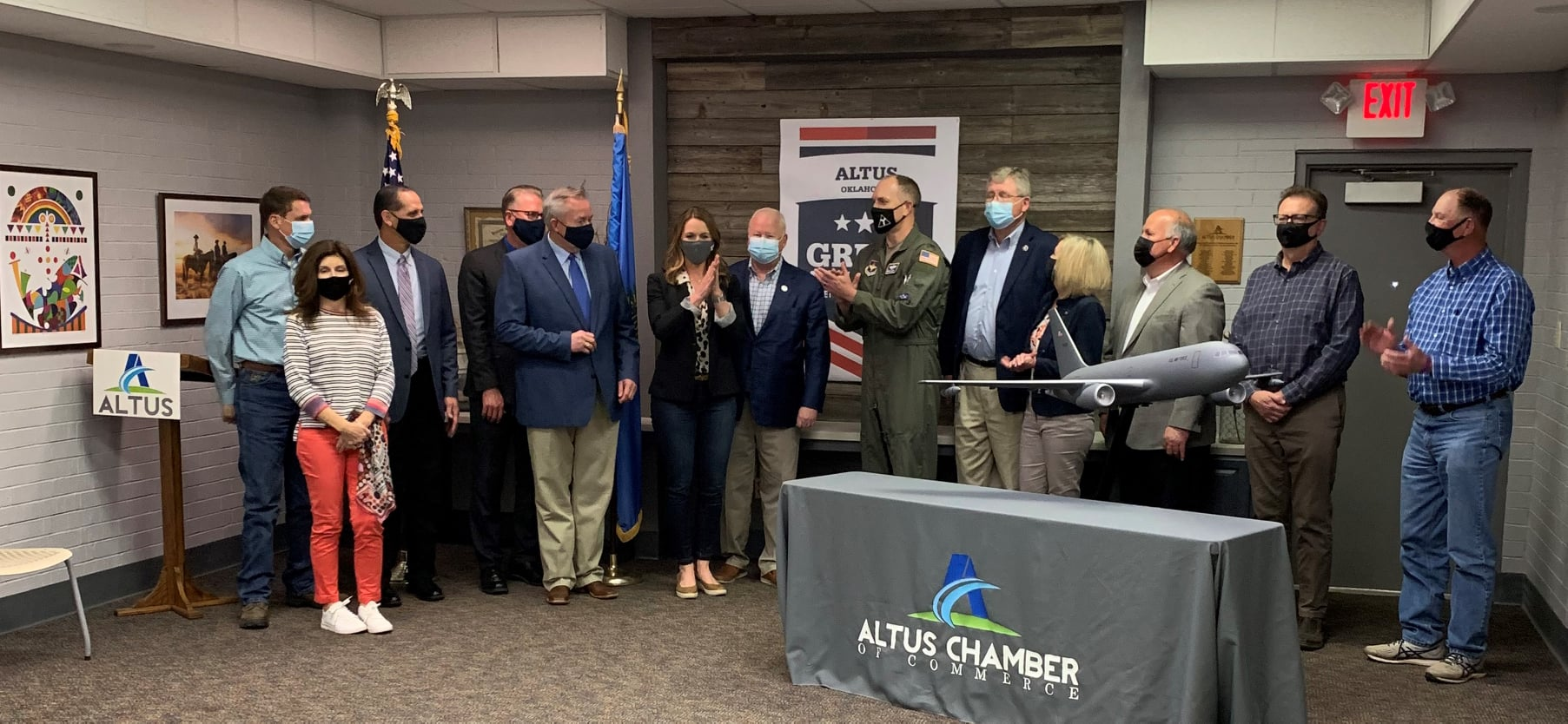 A group of people stand behind a model airplane and Altus Chamber of Commerce sign