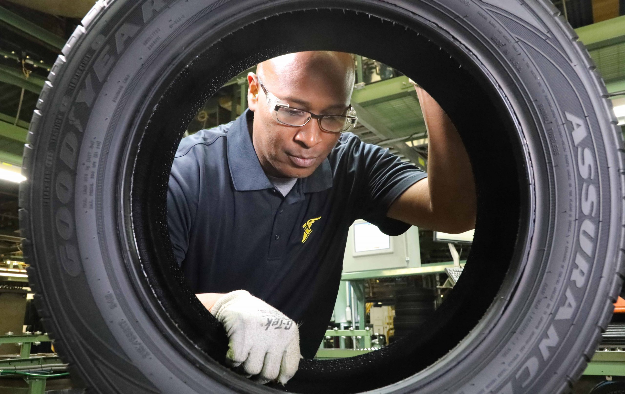 A worker handles a new vehicle tire in the Goodyear manufacturing plant