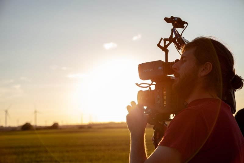 A videographer operates a small camera with an expansive field and wind turbines in the background