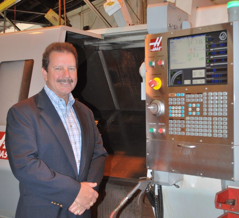 Mike Mills stands next to an industrial machine