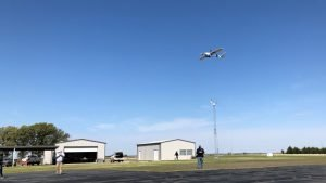 A drone aircraft flies low over people standing in a small airfield