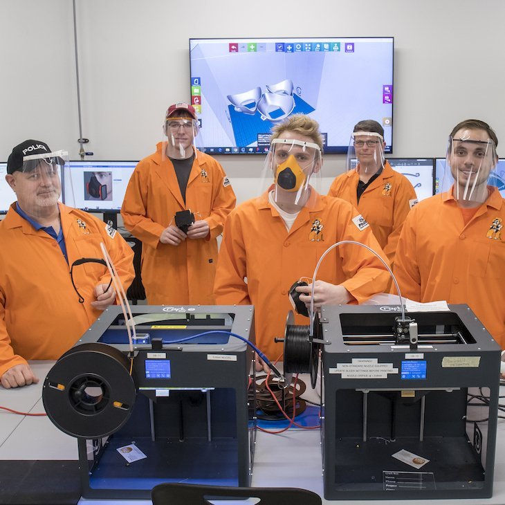 OSU students in protective gear stand behind 3D printers and show off a face mask