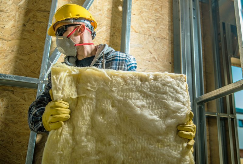Construction Worker Wearing Safety Mask Moving Pieces of Mineral Wool Insulation.