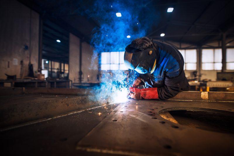 Close up view of worker welding metal construction in industrial workshop.