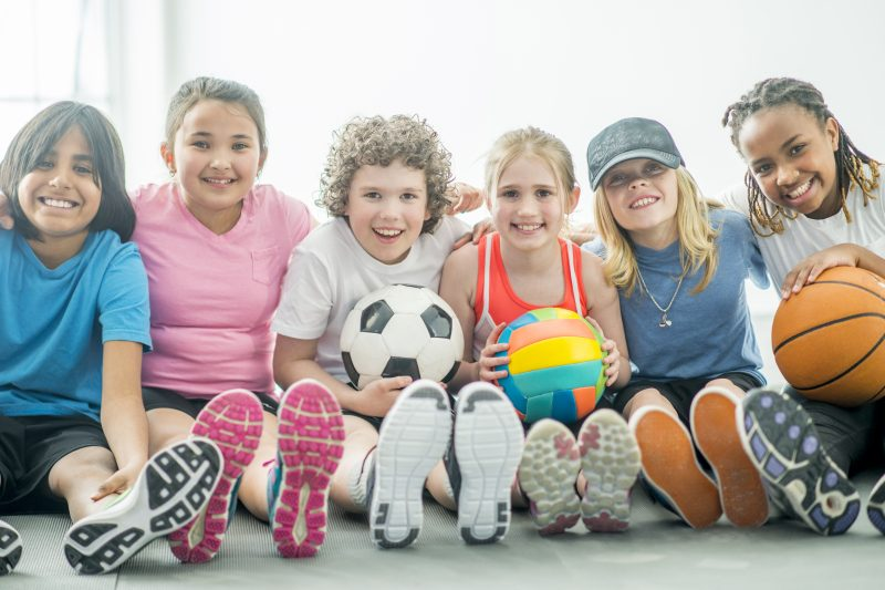 A multi-ethnic group of elementary age children are sitting in a at the gym. They are holding a soccer ball, volleyball, and basketball and smiling while looking at the camera.