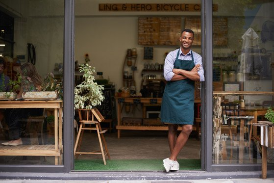 A handsome young man standing in the entrance to his store