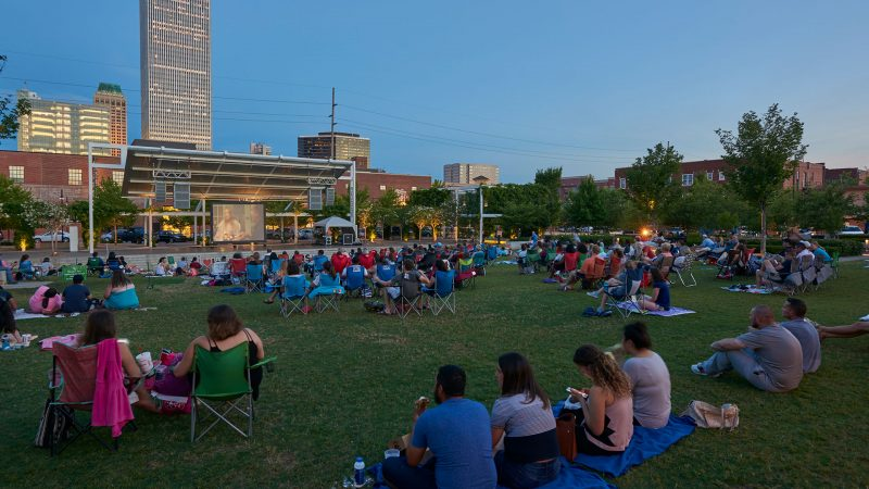 People in lawn chairs watch an outdoor movie on the lawn of Tulsa's Guthrie Green
