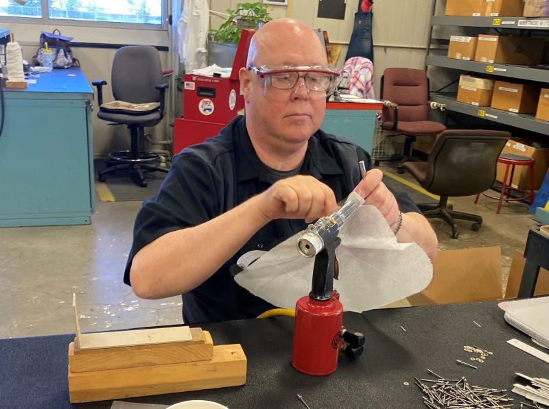 Paul Long, an Aviation Maintenance Technician (AMT) at Tech Ops – Tulsa, assembles a face shield.