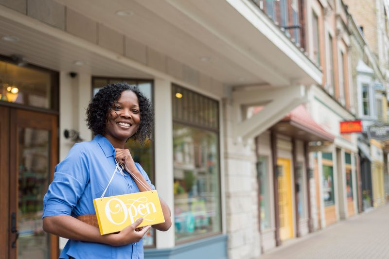 women hold business sign outside shop