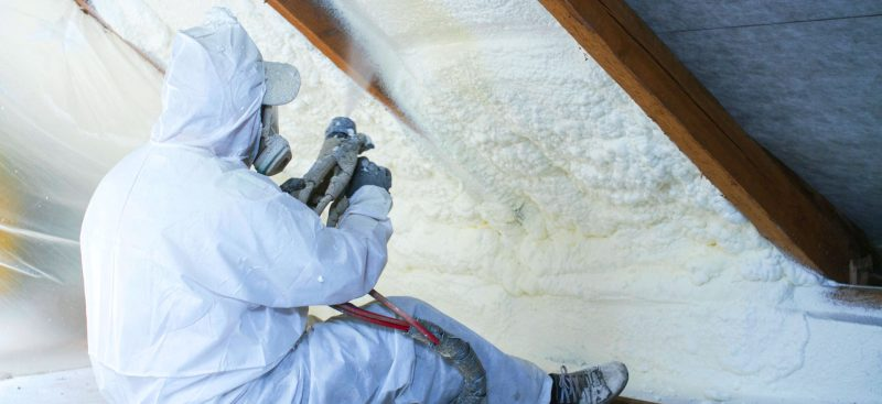 Worker spraying foam insulation