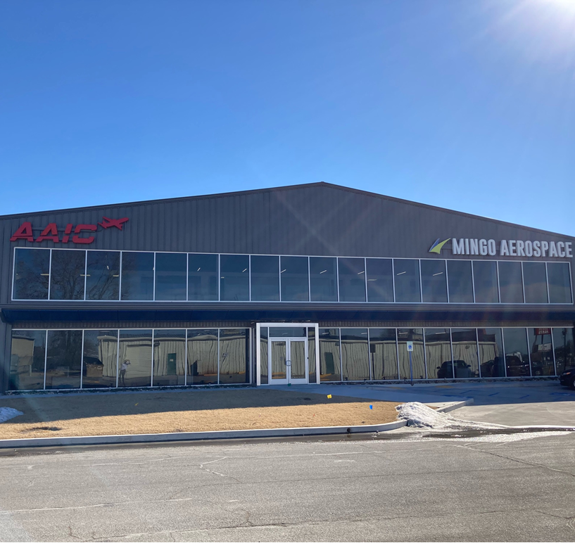 Building with AAIC and Mingo Aerospace signs